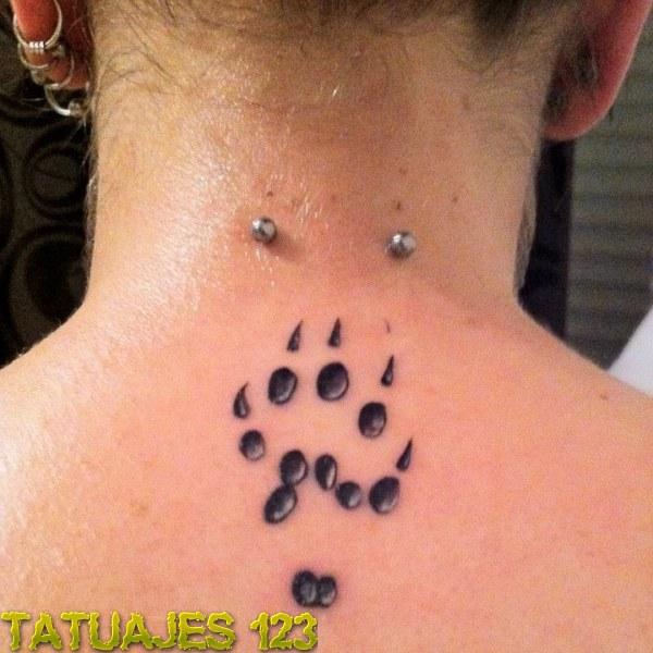 Piercing y tatuaje en la nuca